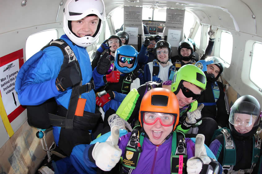 10 Skydivers smiling in the plane