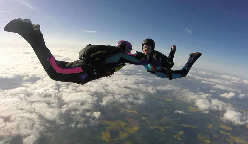 2 skydivers in freefall smiling